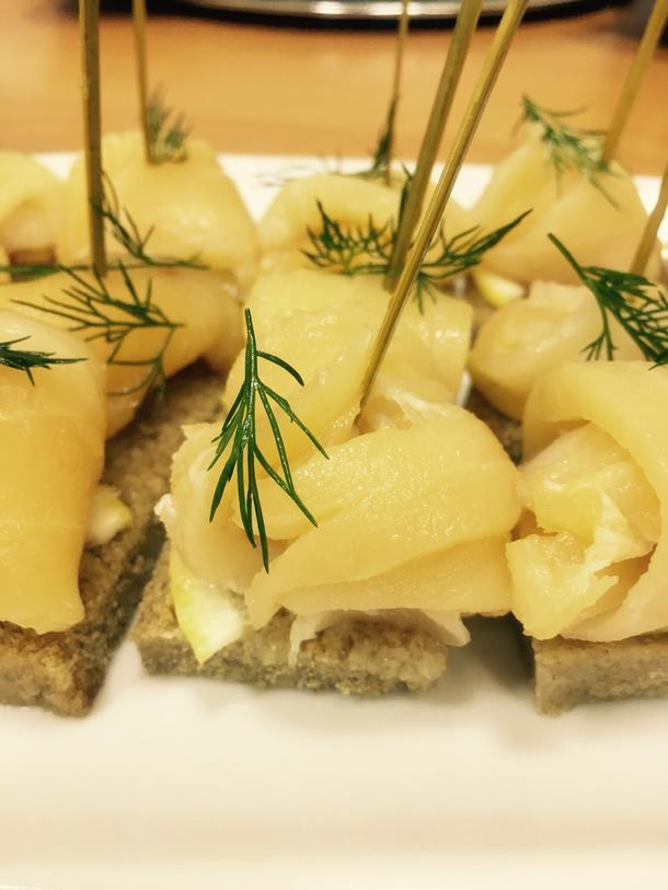 Копченый палтус на тосте из черного хлеба с зеленым луком и лимоном